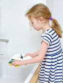 Little girl washing the dishes in the kitchen. — Stock Photo