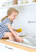 Happy little girl washing the dishes in the kitchen. — Stock Photo