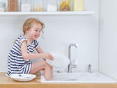 Happy little girl washing the dishes in the kitchen. — Stok fotoğraf