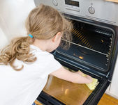 Little girl wipes oven in the kitchen at home. — Stock Photo