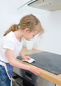 Little girl wipes cooktop in the kitchen at home. — Stock Photo