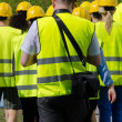 Group of workers in hardhats. View from the back. — Stock Photo