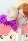 Little girl and mother playing with dollhouse. — Stock Photo