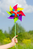 Child hand holding pinwheel against blue sky. — Stock fotografie