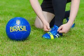 Brazilian Football Confederation. Football player tying his shoes. — Stock Photo