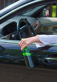 Driving Under the Influence. Female hand with bottle of beer. — Stock Photo