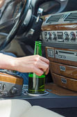Driving Under the Influence. Female hand with bottle of beer. — ストック写真
