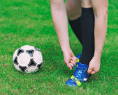 Football player tying his shoes on the field. — Stock Photo