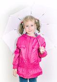 Little girl in bright coat holding umbrella. Indoors. — Stock Photo