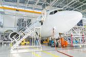 Passenger plane in the hangar. Aircraft maintenance. — Foto de Stock