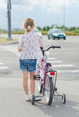 Little girl with bicycle on zebra crossing. — Stok fotoğraf