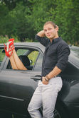 Man posing near the car with woman legs out the window. — Stock Photo