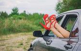 Kadının bacakları araba pencereden dışarı. — Stok fotoğraf
