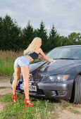 Sexy young blonde woman washes sport car. — Stock Photo