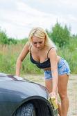 Sexy woman washing car with sponge. — Stock Photo