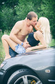 Sensual couple making love on the car's hood. — Stock Photo