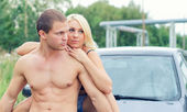 Sexy young couple siting on the car's hood. — Stock Photo