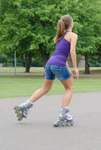 Женщина является катание на коньках роликовых коньков в парке. — Стоковое фото