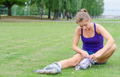 Pretty girl sitting on the grass and putting on inline skates. — Stock Photo