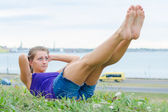 Pretty woman doing exercises for the abs in the park. — Stock Photo