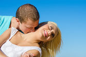 Romantic young couple kissing against blue sky. — Stock Photo