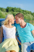 Romantic young couple kissing on the car's hood. — Stock Photo