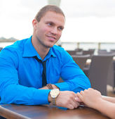 Man making proposal to woman in outdoor cafe. — Photo