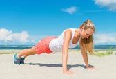 Mujer haciendo flexiones en la playa. — Foto de Stock