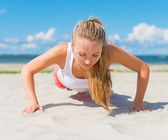 Woman doing push-ups on the beach. — Stockfoto