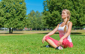 Young woman doing yoga in the park. — Stock Photo