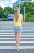 Woman crossing the road at pedestrian crossing. — Stockfoto