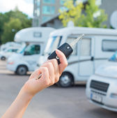 Woman's hand with key against campervans background. — Stock Photo