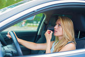 Beautiful young woman applying make-up while driving car. — Stockfoto