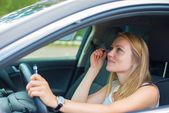 Beautiful young woman applying make-up while driving car. — Stock Photo