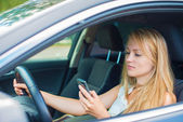 Beautiful young woman writing sms while driving car. — Stock Photo