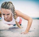 Woman doing push-ups on the beach. Vintage effect. — Stock Photo
