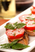 Bruschetta with tomato, mozzarella and basil with a glass of win — Stock Photo