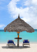 Thatched hut on a white sand beach in Aruba — Stock Photo