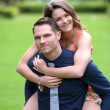 Happy woman jump on man's back smiling couple have fun — Stock Photo