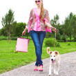 Woman with shopping bags and her dog - Stock Photo