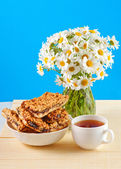 Cookies, cup of tea and a bouquet of daisies — Stock Photo