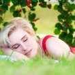 Stock Photo: Woman lying in the grass and dreaming
