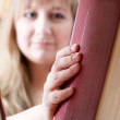 Woman takes a book from the shelf — Stock Photo #26173023