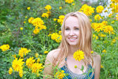 Laughing woman among flowers — Stock Photo