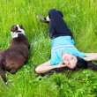 Smiling woman lying on the grass with dog — Stock Photo
