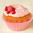 Cupcake with whipped cream and redcurrant — Stock Photo