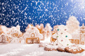 Christmas gingerbread with falling snow — Stock Photo