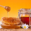Honey in jar with honeycomb and wooden drizzler — Stock Photo #39423975
