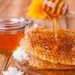 Honey in jar with honeycomb and wooden drizzler — Stock Photo #39424283