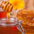 Honey in jar with honeycomb and wooden drizzler — Stock Photo #39426089